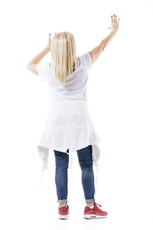 Rear view of mid age woman with raised hands lifting or holding invisible wall or ceiling. Full body length isolated on white background. 版權商用圖片 - 143976598