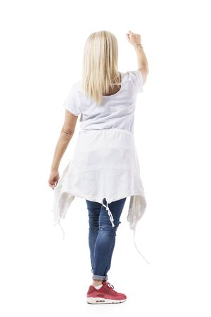 Back view of mid age blond casual woman shopper with raised hand reaching for product. Full body length isolated on white background.