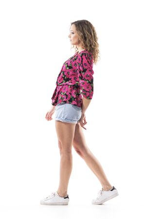 Sad thoughtful young woman in summer casual clothes walking and looking away. Side view. Full body isolated on white background.