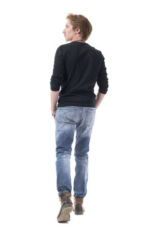 Behind of young confident handsome red hair man walking away and looking at side with hands in pockets. Full body length isolated on white background.  Zdjęcie Seryjne