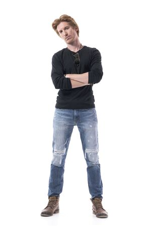 Suspicious distrustful young man with crossed hands looking at camera doubtfully and skeptically. Full body length isolated on white background.