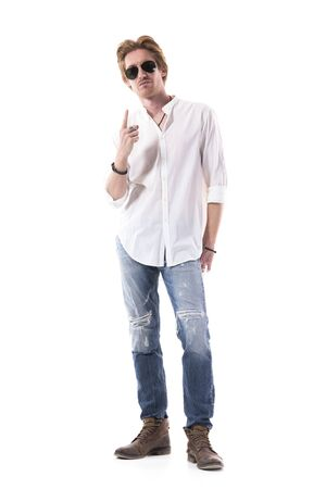 Cool attitude young guy in stylish clothes with sunglasses pointing finger up above. Full length portrait isolated on white background.