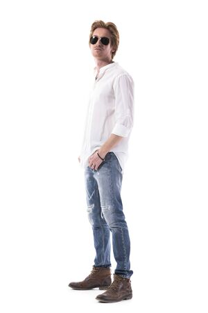 Side view of confident cool fashionable young ginger man with sunglasses posing at camera. Full length portrait isolated on white background.