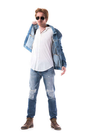 Tough confident handsome man with attitude in jeans removing jacket staring at camera. Full body length isolated on white background.