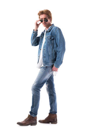 Serious displeased young stylish man in jeans looking above the glasses at camera with strict look. Full body length isolated on white background.