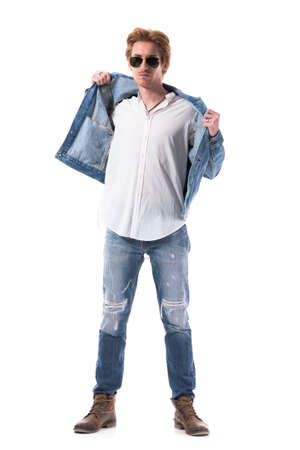 Confident young handsome man in jeans getting dress put on jeans jacket. Full body length isolated on white background.