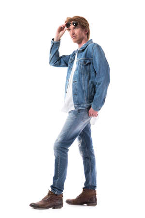 Macho photogenic stylish cool man in jeans holding sunglasses looking up. Full body length isolated on white background.