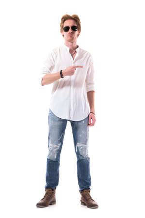 Handsome stylish man advertising and pointing finger at side empty space. Full body length isolated on white background.