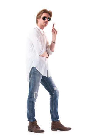 Confident young attractive man in jeans with sunglasses having idea pointing finger up. Full body length isolated on white background.