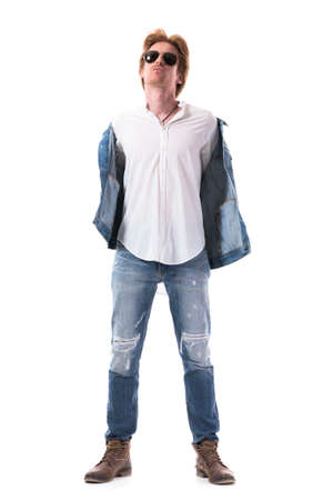 Dominant cocky handsome young self assured man undressing taking off jacket looks at camera. Full body length isolated on white background.