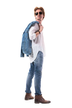 Side view of photogenic young man in jeans carrying jacket looking back over shoulder. Full body isolated on white background.