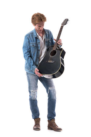 Young stylish guitarist holding and checking guitar getting ready for playing. Full body isolated on white background.