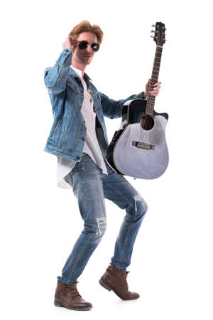 Confident young redhead man in jeans posing with acoustic guitar holding sunglasses. Full body isolated on white background.