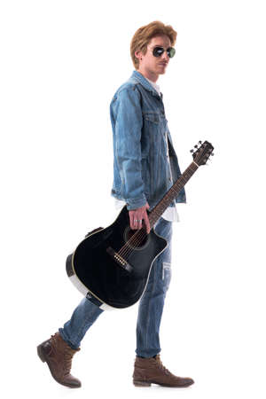 Profile view of redhead young man in jeans walking and carrying acoustic guitar. Full body isolated on white background.