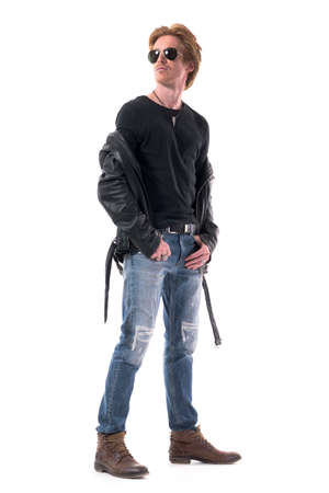 Handsome redhead man fashion model posing with lowered leather jacket in biker style clothes. Full body isolated on white background. 免版税图像