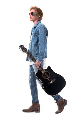 Side view of confident man guitar player walking carrying guitar and looking ahead. Full body isolated on white background. Zdjęcie Seryjne