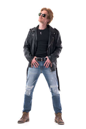 Cool confident masculine rocker posing with thumbs in belt and finger out looking up. Full body isolated on white background. Zdjęcie Seryjne