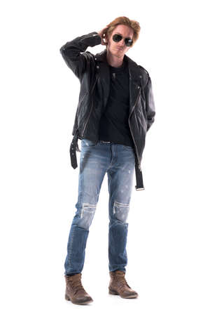 Suspicious uncertain young stylish rocker or biker looking at camera scratching head. Full body isolated on white background. 免版税图像