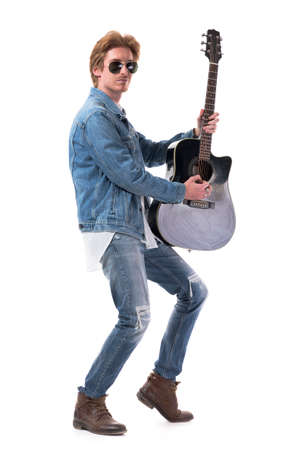 Skillful talented young stylish man guitarist playing guitar holding it vertically. Full body isolated on white background.