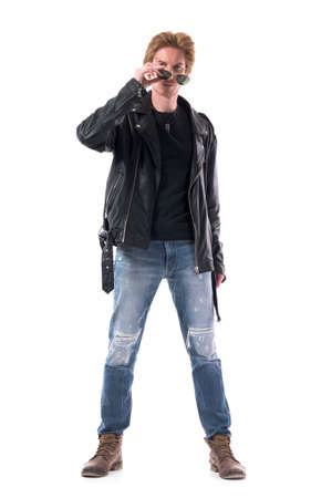 Macho young stylish man fashion model in leather jacket and jeans remove sunglasses. Full body isolated on white background.
