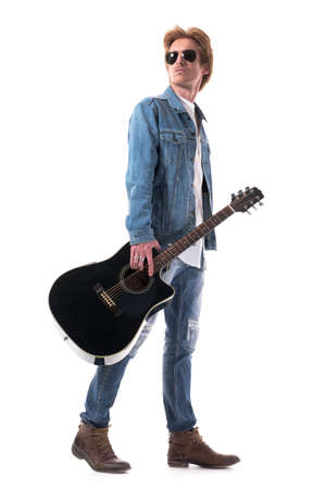 Side view of masculine guitarist carrying guitar walking and looking back over shoulder. Full body isolated on white background.