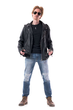 Serious young rocker style man in leather jacket and worn out boots getting dressed looks at camera. Full body isolated on white background. Zdjęcie Seryjne