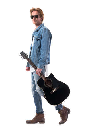 Cool macho rocker male in jeans walking and holding acoustic guitar wearing sunglasses. Full body isolated on white background. 免版税图像