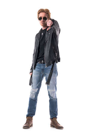 Dominant macho displeased young biker style man showing thumb down gesture. Full body isolated on white background. Zdjęcie Seryjne