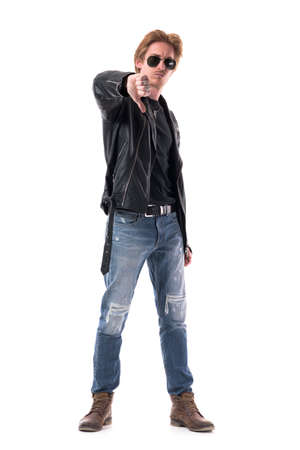 Displeased young stylish man in black leather jacket and jeans showing disapproval hand sign. Full body isolated on white background.
