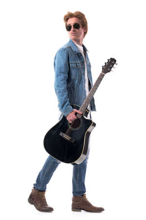 Side view of stylish man wearing jeans jacket boots with sunglasses walking carrying guitar look behind. Full body isolated on white background.