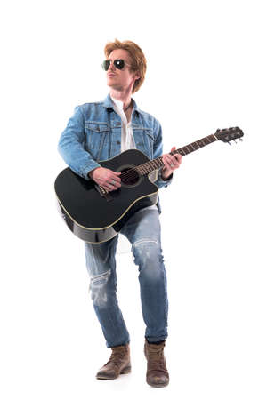 Man guitarist musician paying acoustic guitar with skill and passion wearing jeans. Full body isolated on white background. Zdjęcie Seryjne