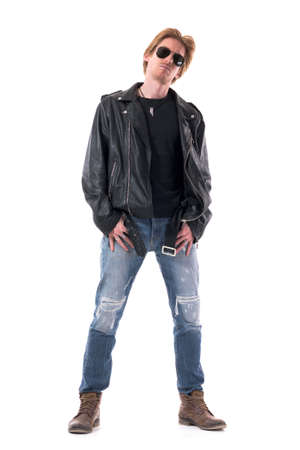 Confident serious rocker or motorcyclist with thumbs in pockets wearing sunglasses. Full body isolated on white background.
