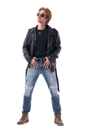 Happy stylish biker or rocker posing with thumbs in belt looking up with smirking smile. Full body isolated on white background. 免版税图像