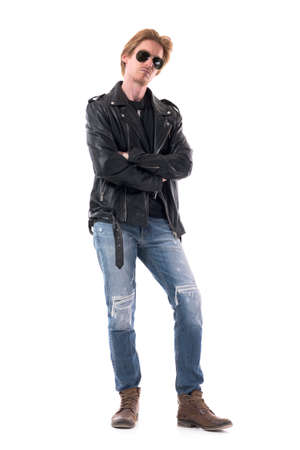 Serious confident stylish man in rocker or biker clothes looking at camera with crossed hands. Full body isolated on white background.