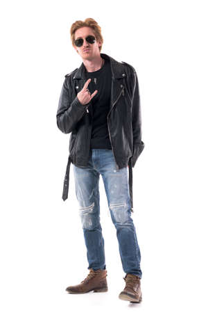 Macho rocker man showing two finger horns or devil hand sign gesture in black leather jacket. Full body isolated on white background.