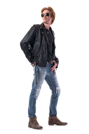 Macho confident young man in biker leather jacket and jeans posing and looking back. Side view. Full body isolated on white background.