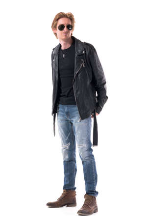 Side view of stylish masculine young redhead man in biker clothes with hands behind. Full body isolated on white background. 免版税图像