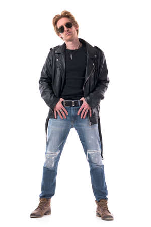 Stylish young handsome man wearing ripped jeans boots and leather jacket posing as model. Full body isolated on white background.