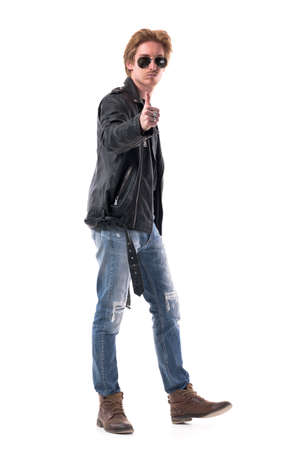Cool stylish confident macho rocker or biker showing thumbs up approval hand sign. Full body isolated on white background. Zdjęcie Seryjne