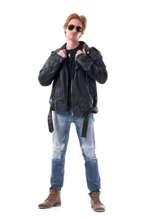 Confident redhead rocker or biker getting dressed put on leather jacket. Full body isolated on white background.