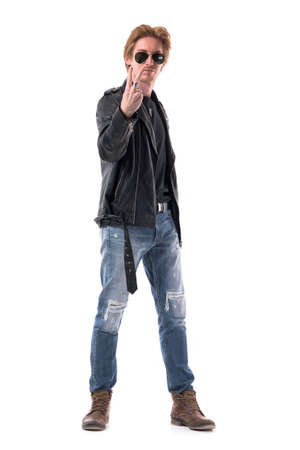 Macho young adult redhead man in leather jacket and boots showing victory two fingers gesture at camera. Full body isolated on white background. 免版税图像