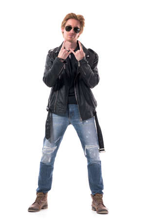 Stylish macho attitude young redhead man in leather jacket showing heavy metal horns hand sign. Full body isolated on white background.