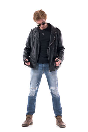 Confident stylish rocker buying clothes trying on black leather jacket looks down. Full body isolated on white background. 免版税图像