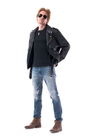 Confident motorcyclist in leather jacket with sunglasses and boots posing with hands in back pockets. Full body isolated on white background.