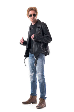 Side view of handsome biker in jeans and black leather jacket wearing boots getting dressed. Full body isolated on white background. 免版税图像