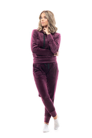 Cute calm young woman in burgundy plush sweatsuit posing with finger on cheek. Full body isolated on white background.
