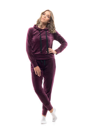 Confident young woman in burgundy hooded sweatshirt and sweatpants in socks posing. Full body isolated on white background.