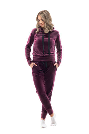 Comfy young relaxed woman with hands in pockets wearing short socks and burgundy sweatsuit posing. Full body isolated on white background.