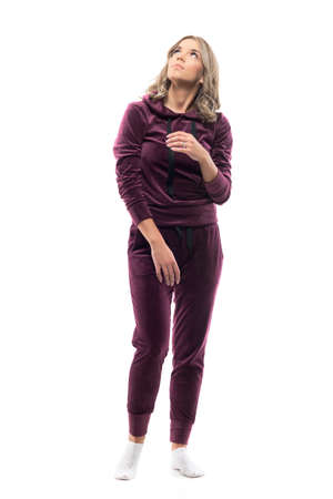 Distracted and scared young woman in home wear sweatsuit looking up. Full body isolated on white background.