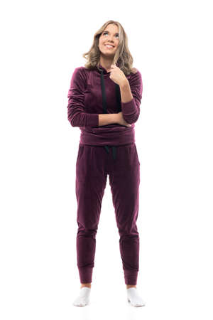 Happy young woman in leisurewear tracksuit looking up having idea and smile touching hair. Full body isolated on white background.